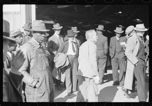 """Itinerant preacher spreading """"religion"""" to farmers outside warehouse while tobacco auction sales are going on. Durham, North Carolina"""