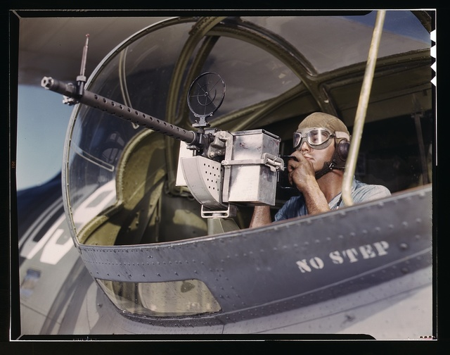 Jesse Rhodes Waller, A.O.M., third class, tries out a 30-calibre machine gun he has just installed on a Navy plane, Naval Air Base, Corpus Christi, Texas