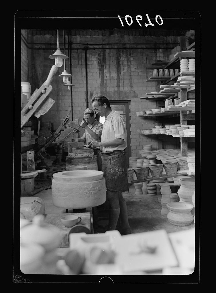 "Jewish factories in Palestine on Plain of Sharon & along the coast to Haifa. Haifa. The ""Kadar"" Ltd. Ceramics. The potters work at the potters wheels"