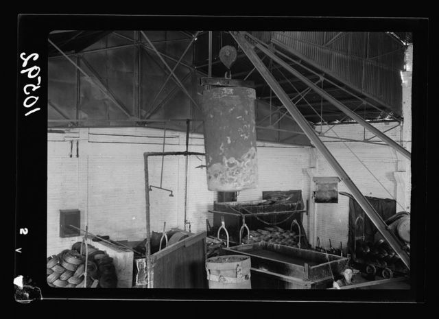 """Jewish factories in Palestine on Plain of Sharon & along the coast to Haifa. Petah-Tikvah. Wire drawing & nail factory. """"Barzelit,"""" Ltd. Red hot cylinder containing wire being removed from oven by crane"""