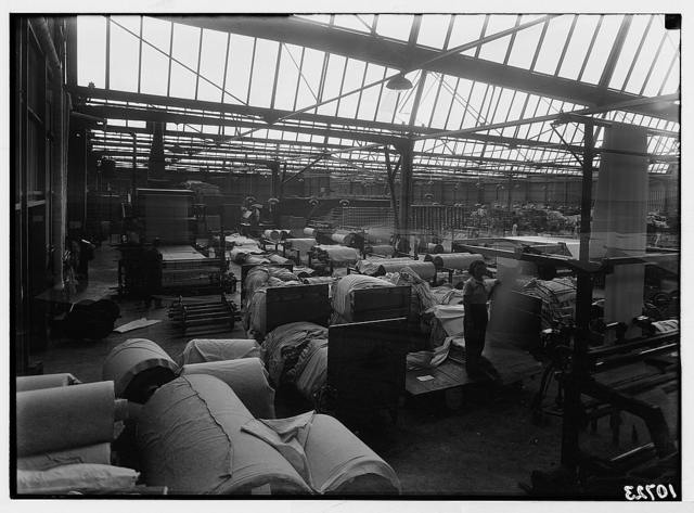 "Jewish factories in Palestine on Plain of Sharon & along the coast to Haifa. Near Acre. Kfar-Ata. The ""Ata"" Textile Co. Section in the main house showing cloth in various states of finishing"