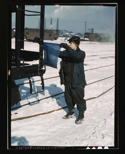 John Paulinski, car inspector, blue flagging a train for inspection, at Corwith yard, Santa Fe RR trip, Chicago, Ill.