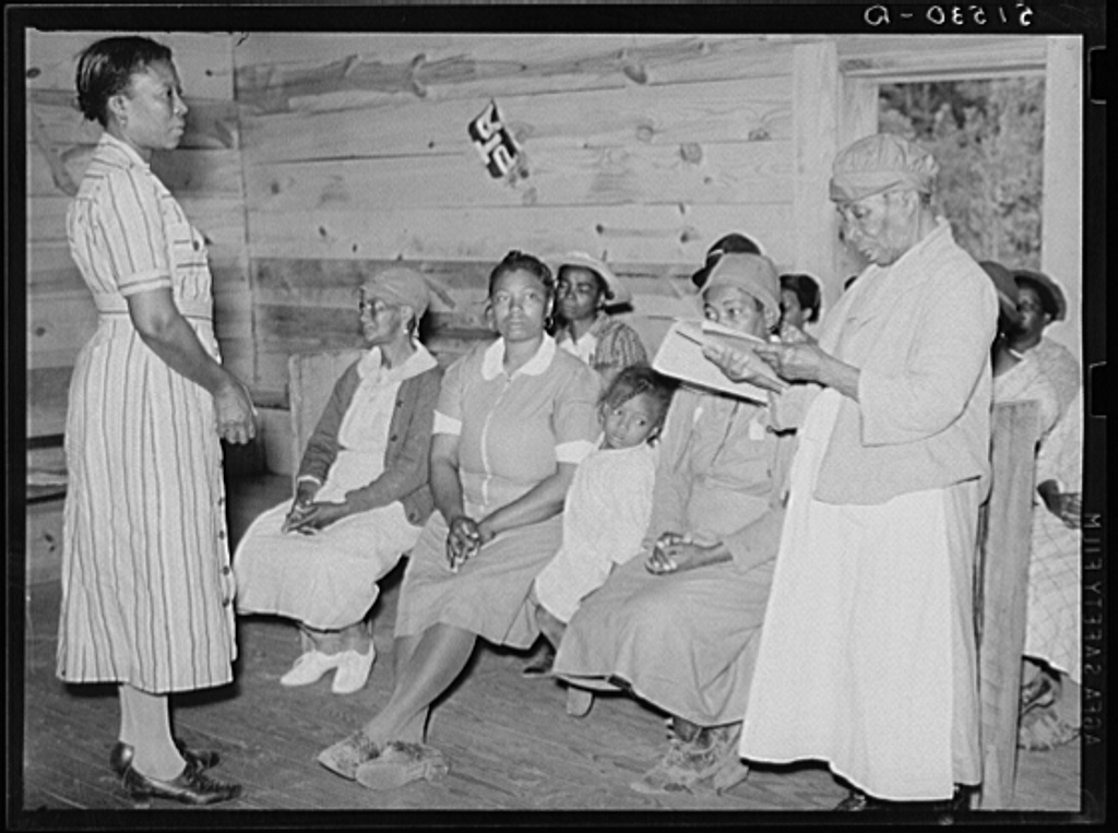 Juanita Coleman (Miss or Mrs.), teacher and NYA (National Youth Administration) leader, listening to one of her pupils in adult class read. She has just learned, is eighty-two years old and best in class. They meet in old church building for reading, writing, arithmetic, and general discussion and educational activities. Gee's Bend, Alabama