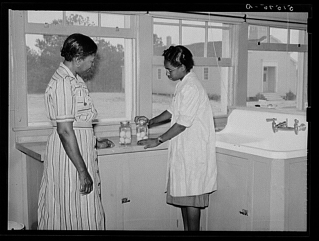 Juanita Coleman, NYA (National Youth Administration) leader and teacher, helps Sally Titus preserve some eggs. Through this activity the girl has bought some badly needed eyeglasses. Gee's Bend, Alabama