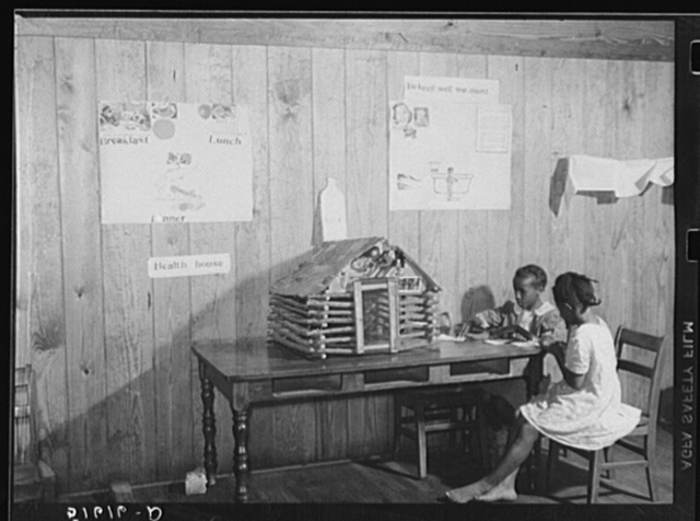 Juanita Eygran and Jeredine Burman cutting out health pictures to paste on second and third grades health house. Flint River Farms, Georgia