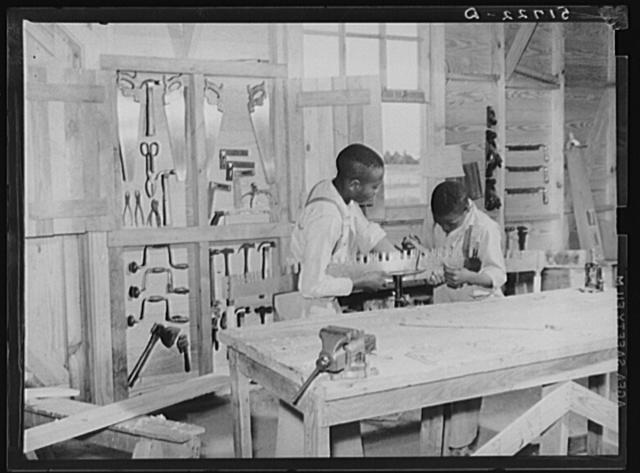 J.W. West and John Young sharpening crosscut saw in school shop class. Flint River Farms, Georgia