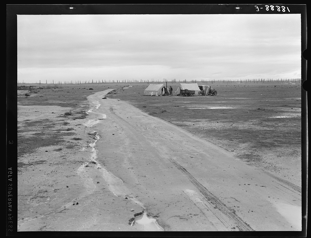 Kern County, California. Camp of two related families seen from U.S. 99. Oil field beyond. Came to California in 1920 from Missouri. Father had job for eight years. Was gang foreman on Los Angeles Aqueduct; laid off two months ago. Now on way north looking for work. Doesn't want to go on Work Projects Administration (WPA)