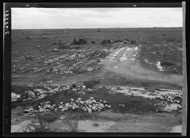 Kern County. Debris left out on the flats where squatters' camp stood during work season. These are common sights after the migrants have left