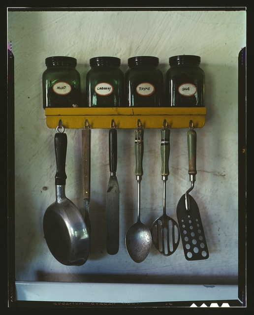 [Kitchen utensils hanging below a spice rack with mint, caraway, thyme, and sage jars]