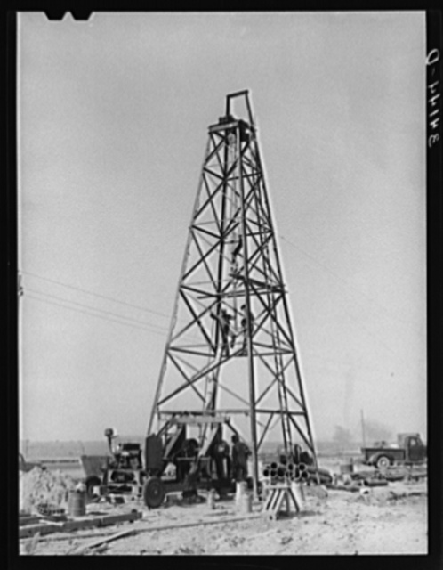 Lifting casing upon the derrick to finish a water well for irrigation purposes on farm near Garden City, Kansas