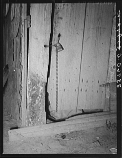 Locked door of shack. Mays Avenue camp, Oklahoma City, Oklahoma. The sense of possession is just as strong in this downtrodden group as in any other. See general caption no. 21