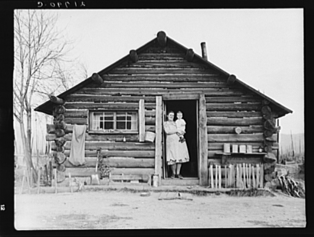 Log house now occupied and enlarged by the Halley family. Mrs. Halley in doorway with youngest child. Bonner County, Idaho. See general caption 51