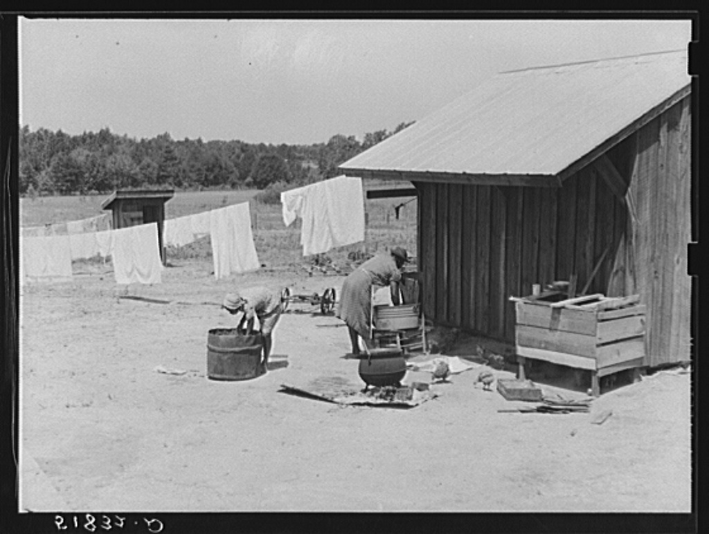 Lonny Smith's wife and daughter doing laundry by new smoke and washhouse in their yard. Flint River Farms