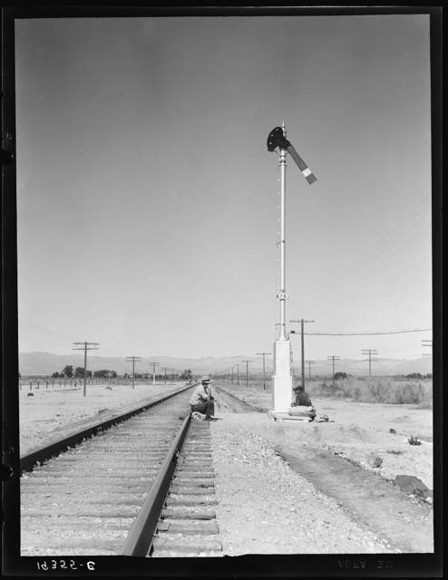 """Looking east down the railroad track, near Calipatria, California. Single men, itinerants with """"bindles"""" waiting for the freight"""