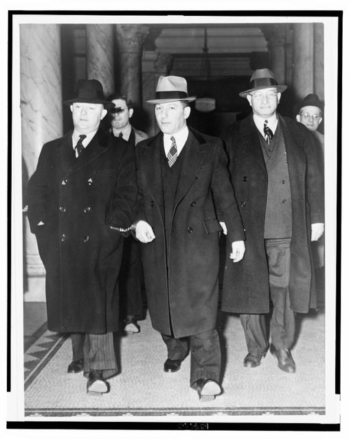 "[Louis ""Lepke"" Buchalter, center, handcuffed to J. Edgar Hoover, on the left, with another man on the right, at entrance to courthouse] / World Telegram photo by Al Aumuller."