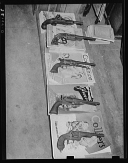 Magazines weighted down with pistols. Drugstore, Gonzales, Texas