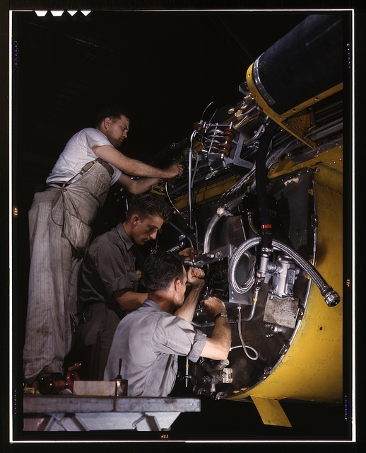Making wiring assemblies at a junction box on the fire wall for the right engine of a B-25 bomber, North American Aviation, Inc., [Inglewood], Calif. Forward of this wall will be mounted one of the two 1,700-horsepower Wright Whirlwind engines which carry the B-25 through performances up to Altitudes of 25,000 feet