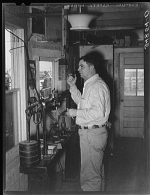 Man in office at stockyards. After cattle are sold at auction he calls out to the keepers in the pens to put cattle with certain numbers in certain pens. In this way each buyer's cattle are separated and delivery is facilitated. Stockyards, San Angelo, Texas