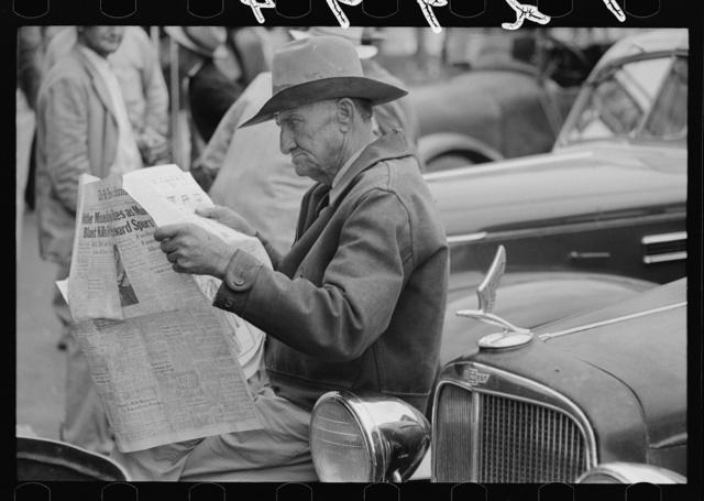 Man sitting on automobile fender reading a newspaper, market square, Waco, Texas