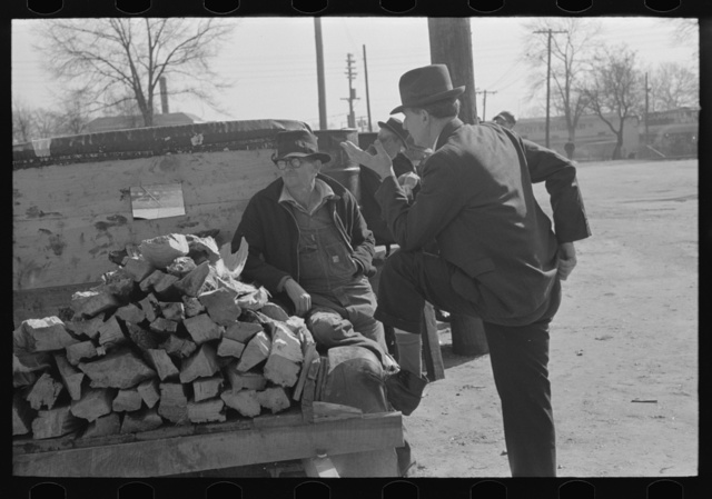 Man talking to farmer with truckload of wood, Laurel, Mississippi