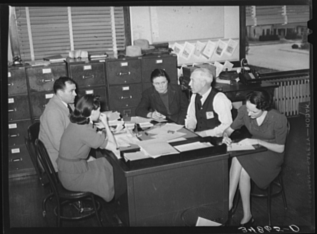 Meeting of county FSA (Farm Security Administration) supervisors and assistant to determine program for the week. Limited mileage allowance requires careful planning in these large counties so that clients can be visited. San Angelo, Texas