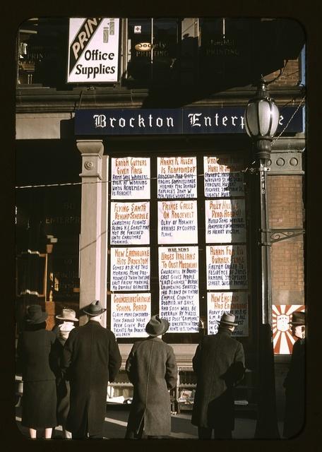 Men and a woman reading headlines posted in street-corner window of Brockton Enterprise newspaper office on Christmas Eve, Brockton, Mass.