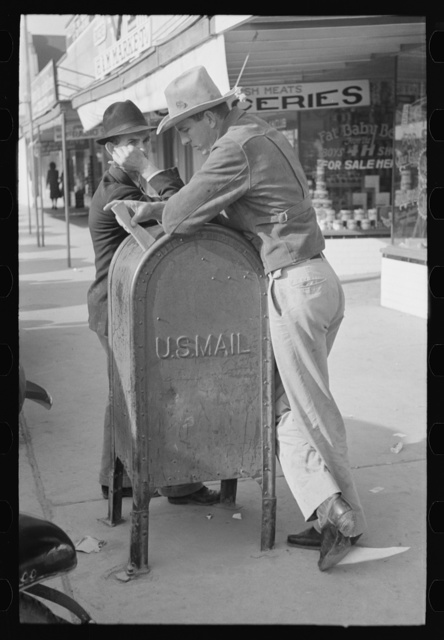 Men leaning on mailbox, Crystal City, Texas