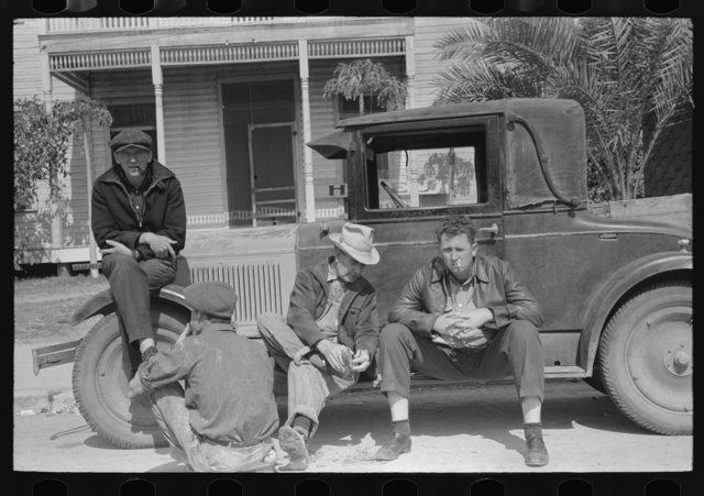 Men sitting on car, street of Raymondville, Texas