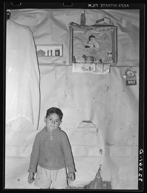 Mexican boy living in corral, Robstown, Texas. Notice the crude wall papering