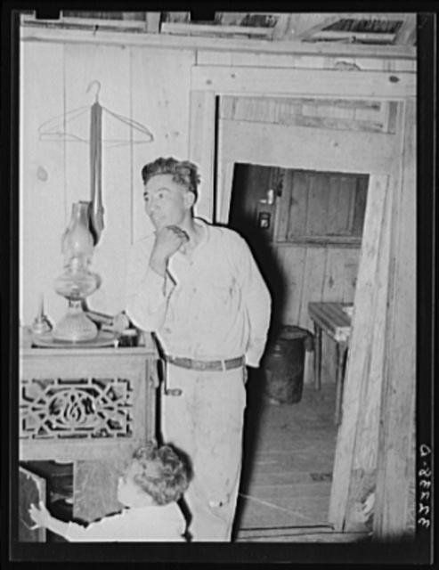 Mexican labor contractor and child in their home. Notice that the doorway shows the construction of the house. Two houses have been joined together. Robstown, Texas