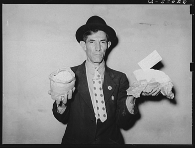 Mexican pecan workers union official displaying relief supplies which are supposed to feed a family of three for two weeks. The articles shown are beans and butter. San Antonio, Texas
