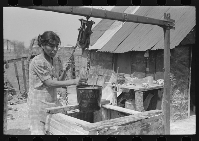 Mexican woman drawing a bucket of water from backyard well, San Antonio, Texas