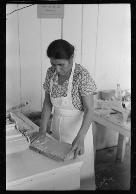 Mexican woman flattening and shaping tortillas between two boards hinged together, San Antonio, Texas