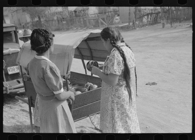 Mexican women buying pottery from street peddler, San Antonio