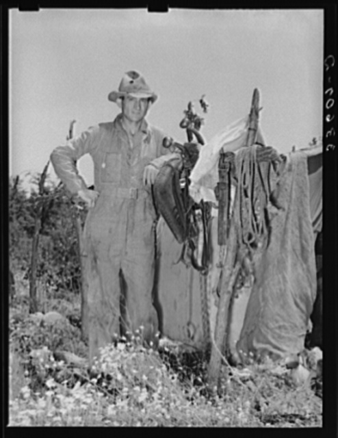 Migrant agricultural laborer standing in front of his tent near Vian, Oklahoma. Sequoyah County