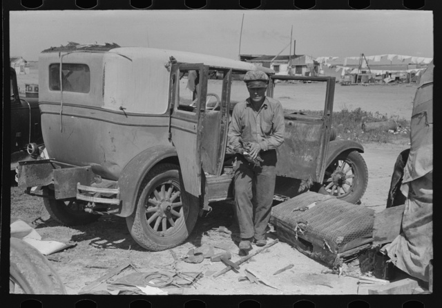 Migrant auto wrecker in front of car which he will dismantle, Corpus Christi, Texas