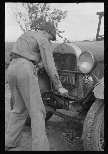 Migrant boy getting ready to crank his car, Muskogee, Oklahoma