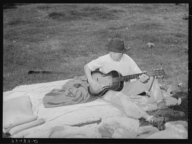 Migrant boy playing the guitar on pallet while camped near Prague, Oklahoma. Lincoln County, Oklahoma