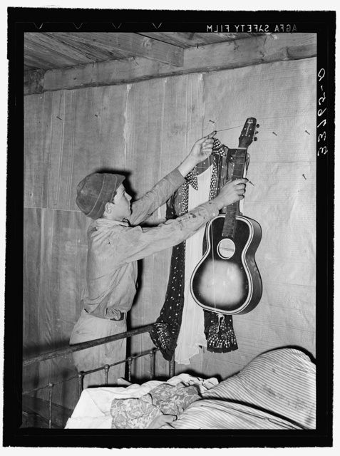 Migrant boy removing guitar before they leave for California. At old homestead near Muskogee, Oklahoma