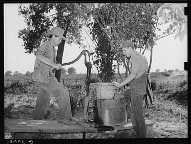 Migrant boys pumping water at their shack home near Muskogee. Muskogee County, Oklahoma
