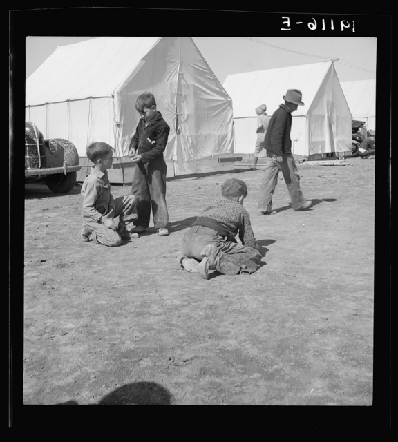 Migrant children in Farm Security Administration (FSA) migratory labor camp. Note type of boots worn by boy shooting marbles which tell his state of origin. Near Calipatria, Imperial County, California