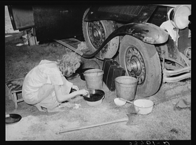 Migrant girl gathering up pots and pans to pack into automobile at roadside camp near Muskogee, Oklahoma. Muskogee County