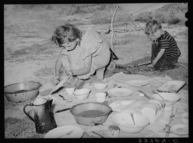 Migrant girl scraping plates after noonday meal along the highway near Muskogee, Oklahoma. Muskogee County