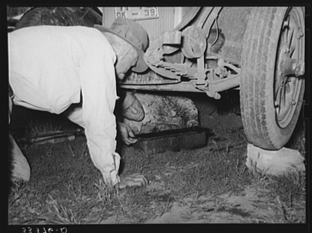 Migrant steeple-jack removing the crank case from his automobile. Near Prague, Oklahoma. When he secures a job, the entire family, consisting of his father and mother, wife and sister, all help with the painting