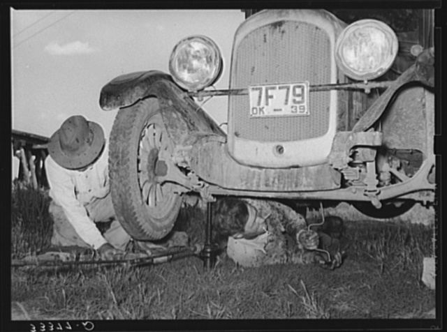 Migrant steeple-jack removing the crank case from his automobile while his father blocks up the front wheel. Near Prague, Oklahoma. When he secures a job, the entire family, consisting of his father and mother, wife and sister, all help with the painting