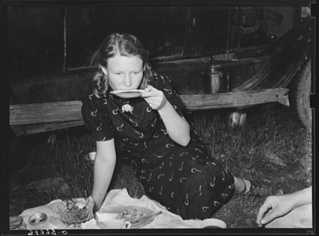 Migrant woman drinking coffee from saucer while camped near Prague, Oklahoma