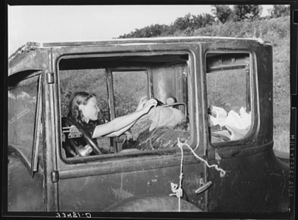 Migrant woman reaching in automobile for supplies while camped near Prague, Oklahoma. Lincoln County, Oklahoma