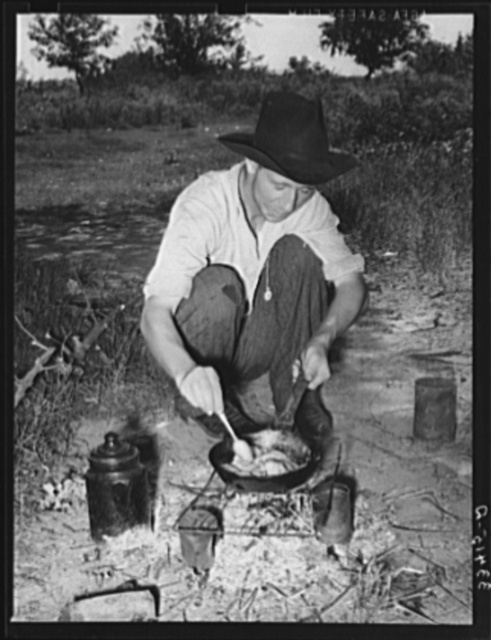 Migrant worker cooking fatback over wood fire in camp near Prague, Oklahoma. Lincoln County