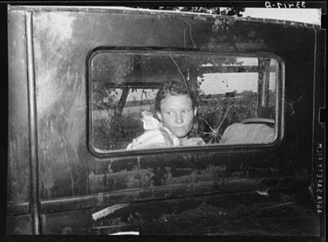 Migrant worker looking through back window of automobile near Prague, Oklahoma. Lincoln County, Oklahoma