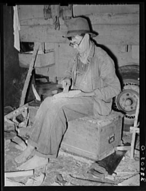 Migrant worker who makes ornaments from horns. He is filing down a wooden block to be used as base for horns. Near Hammond, Louisiana
